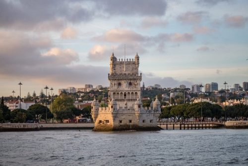 tower-belem-surrounded-by-sea-buildings-cloudy-sky-portugal_181624-10409